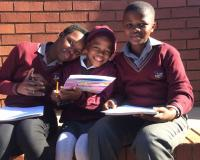 Children at the Meetse School in Pretoria, South Africa with Want a Friend? Be a Friend! booklets. Photo: U of P Vet Students