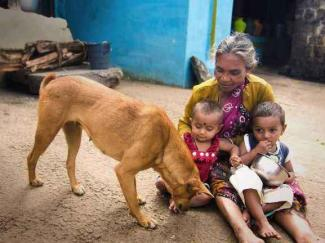 An Indian woman sits with her grandchildren and dog