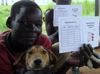 boy smiling with dog and holding up vaccination certificate
