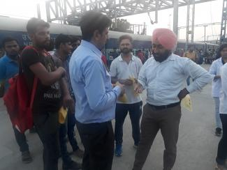 Faculty member addressing the query of passengers at railway station regarding prevention of rabies